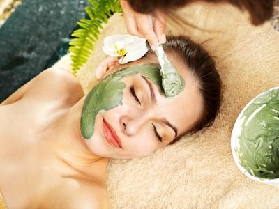 Beautiful woman having clay facial mask apply by beautician.