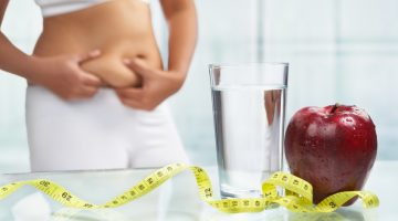 red apple and water with measuring tape on table with female body on sport attire at background for diet concept
